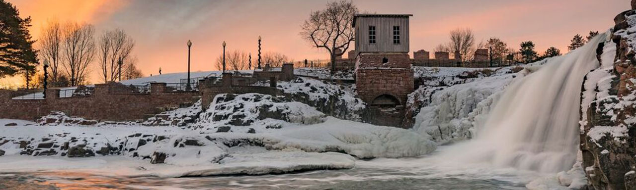 frozen waterfall with old mill in background at sunset