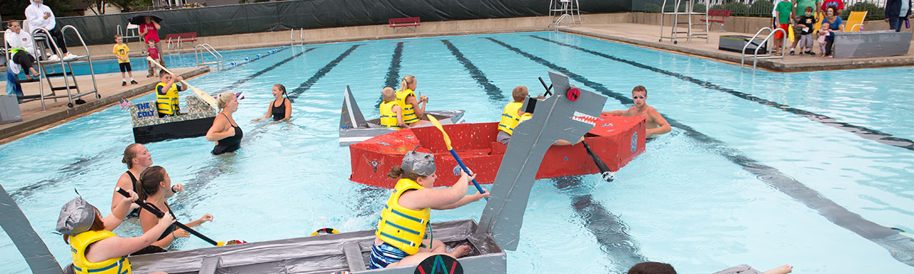 teams of children paddling homemade cardboard boats in a pool