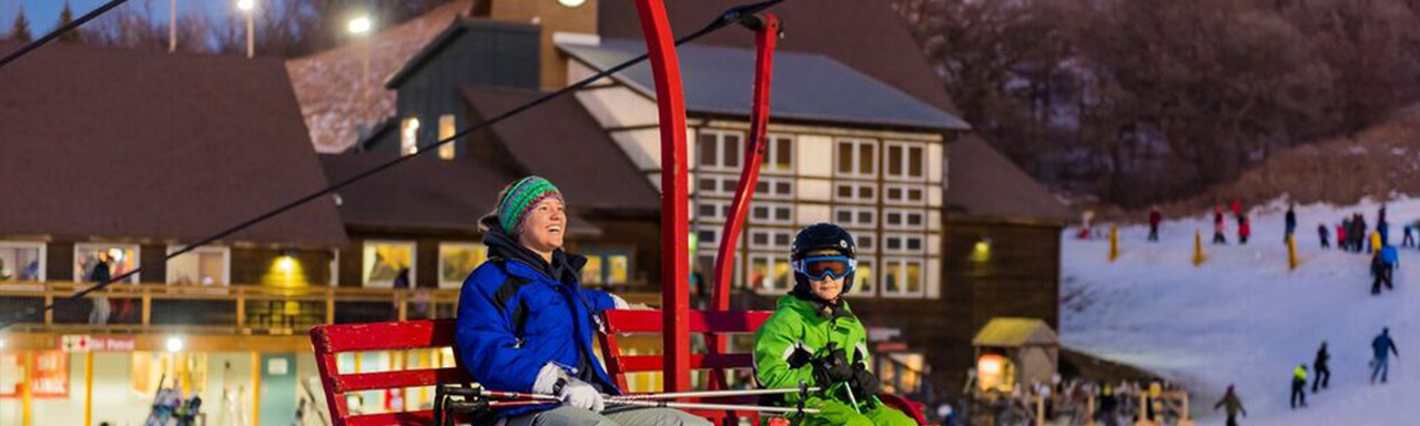 women and child riding a ski lift